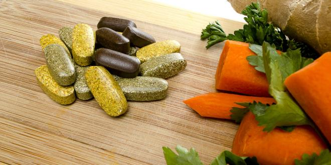 Vitamins and carrots on cutting board